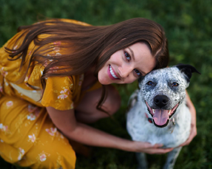 brunette woman in yellow dress smiling and hugging happy cattle dog
